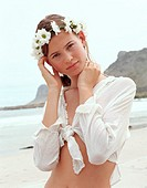 Teenage girl (15-17) on beach wearing floral headdress, portrait