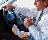 Businessman driving car, fast food in lap, drinking through straw
