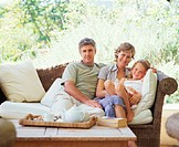 Couple relaxing on wicker sofa with daughter (5-7), portrait