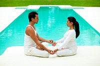 Couple face to face in yoga position near swimming pool, side view