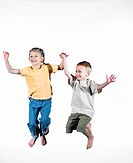Girl and boy (5-7) jumping, holding hands, smiling
