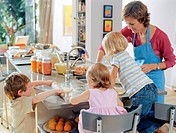 Mother baking with boy and girl (3-5) and girl (15-18 months)