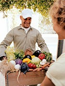 Man delivering crate of vegetables to woman, smiling