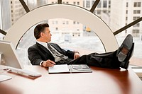 Businessman sitting with feet on desk, looking out of window