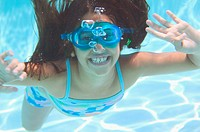 Girl (8-10) with goggles under water, smiling, portrait, close-up
