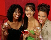 Three young women holding cocktails, smiling, portrait