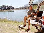 Mature man sitting in back of 4x4 with laptop, using mobile, by lake