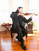 Young man playing violin, eyes closed