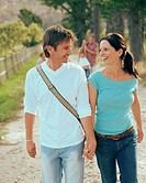 Couple walking along hand in hand, smiling