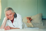 Senior woman lying on bed, resting head on hand, looking down