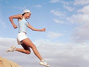 Woman jumping in midair, smiling, side view
