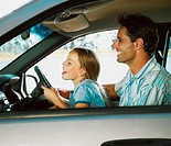 Father and daughter (7-9) in driving seat of car, laughing, side view