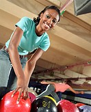 Young woman picking up bowling ball, smiling, portrait, low angle view