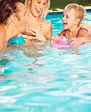 Parents and daughter (4-6) in swimming pool, laughing, close-up