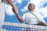 Two senior men shaking hands over tennis net, low angle view