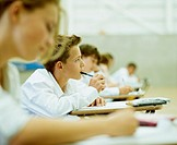 Schoolboy (13-15) in exam  holding pen to mouth, side view