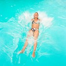 Woman falling backwards into pool, smiling, water splashing