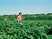 Girl (6-8) running in field with punnet of strawberries, side view