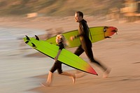 Father and daughter (8-10) running with surfboards (blurred motion)