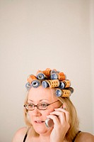Woman using cell phone, wearing curlers in hair