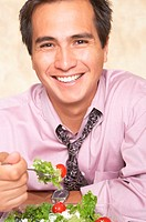 Young businessman eating salad, smiling, portrait