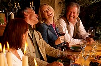Two mature couples at dining table, laughing