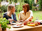 Two mature women preparing food at table in garden