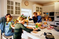 Parents and children (2-10) in kitchen, girls doing homework
