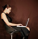 Young woman seated in chair using laptop computer, side view