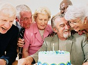 Mature men and women gathered around birthday cake, smiling
