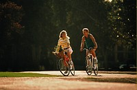Couple riding bicycles,woman in yellow and white,man in green vest