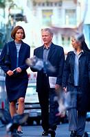 Businesspeople Walking on Urban Sidewalk