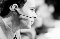 Businessman using telephone headset, close-up, profile (B&W)