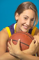 Teenage girl (13-15) holding basketball, smiling, portrait