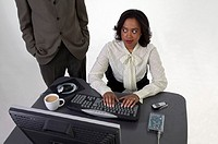 Businessman standing beside young businesswoman using computer at desk