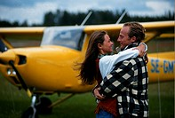 Couple embracing by airplane