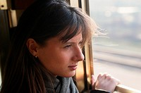 Woman looking through train window, close up