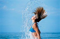 Young woman splashing in sea, side view