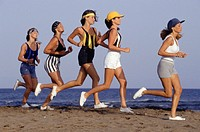 Group of people jogging on beach