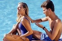 Young man applying suntan cream on girl´s shoulders