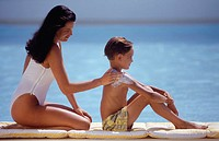 Mother applying sun cream on shoulder of son (8-9) by sea, side view