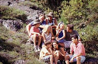Group of friends sitting on stony slope