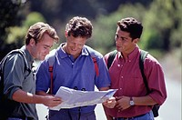 Three young men looking at map outdoors