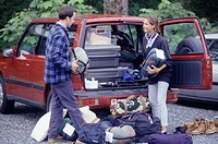 Young couple packing luggage into car
