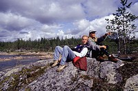 Couple sitting on rock on lakeshore