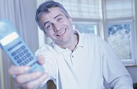 Man holding telephone, smiling, portrait