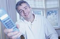 Man holding telephone, smiling, portrait