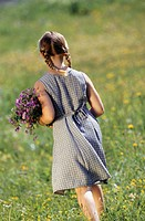Young girl (12-13) walking in meadow with bunch of flowers