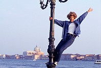 Woman standing on lamp-post waving hand