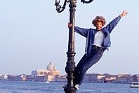 Woman standing on lamp-post waving hand